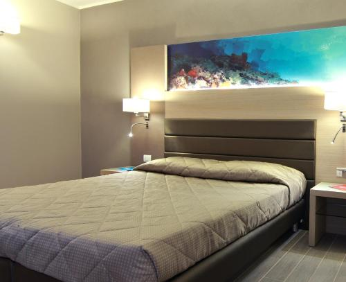 A bed or beds in a room at Alma di Alghero Hotel