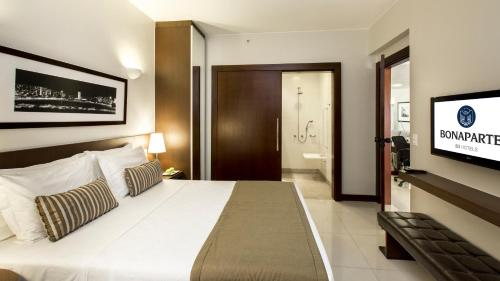 A bed or beds in a room at Bonaparte Hotel