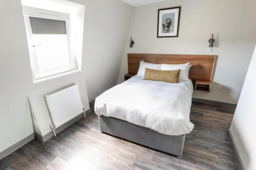 A bed or beds in a room at Broadcroft Hotel