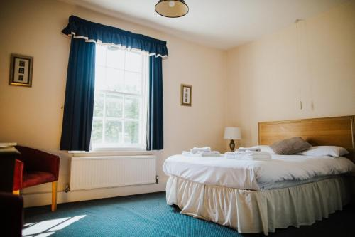 A bed or beds in a room at The Stratton House Hotel