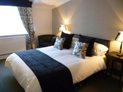 A bed or beds in a room at Deanwater Hotel