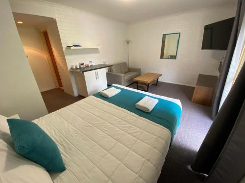A bed or beds in a room at Top of the Town Motor Inn