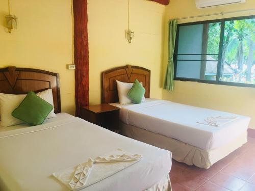 A bed or beds in a room at Koh Ngai Resort