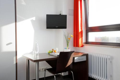 A television and/or entertainment center at Jugendherberge City-Hostel Köln-Riehl