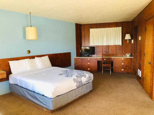 A bed or beds in a room at Curly Redwood Lodge