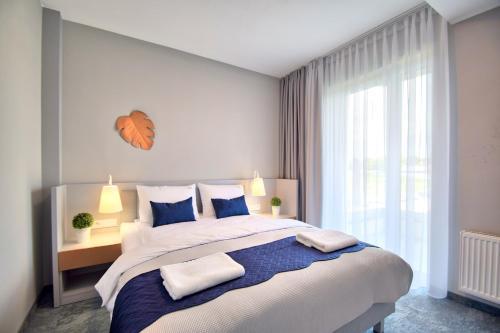 A bed or beds in a room at Savana Resort Mielno
