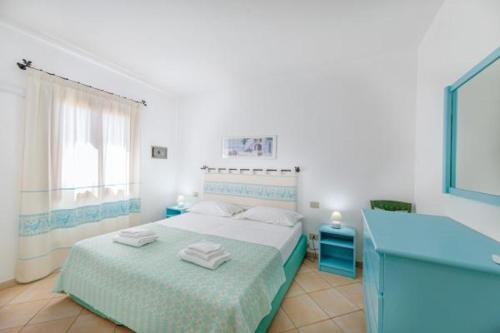A bed or beds in a room at Sardinia Blu Residence
