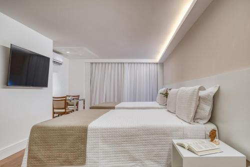 A bed or beds in a room at Hotel Brisa Suites