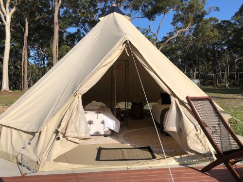 A bed or beds in a room at Bay and Bush Cottages Jervis Bay