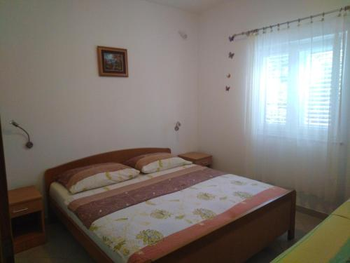A bed or beds in a room at Apartments Tomi
