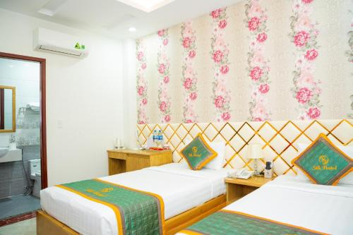 A bed or beds in a room at Silk Hotel near Tan Son Nhat Airport