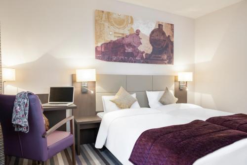 מיטה או מיטות בחדר ב-Mercure Hotel Brussels Centre Midi