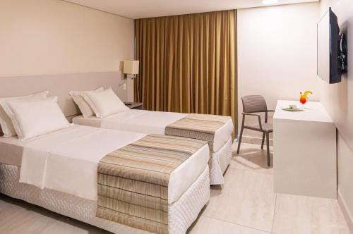 A bed or beds in a room at Ponta Mar Hotel