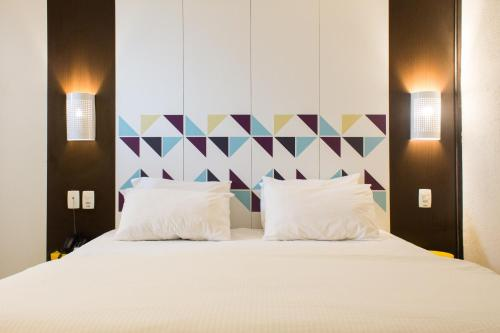 A bed or beds in a room at Master Express Moinhos de Vento Hotel & Coliving