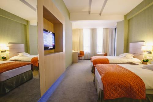 A bed or beds in a room at Hotel Golden Tulip Ana Tower Sibiu