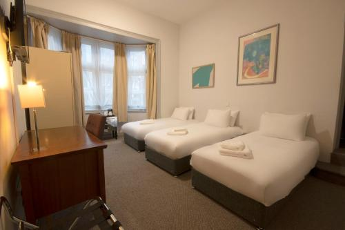 A bed or beds in a room at Royal Hotel Kettering by Paymán Club