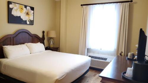 A bed or beds in a room at Mills Park Hotel