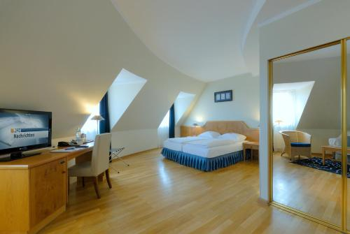 A bed or beds in a room at Golden Tulip Luebecker Hof