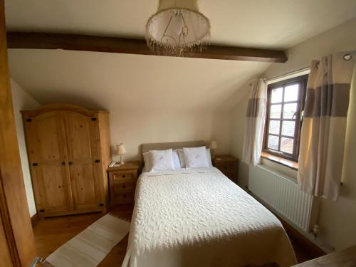 A bed or beds in a room at Thompsons Arms Cottages