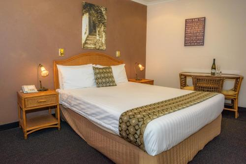 A bed or beds in a room at Sapphire Waters Motor Inn
