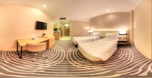 A bed or beds in a room at Regalia Suites & Hotel