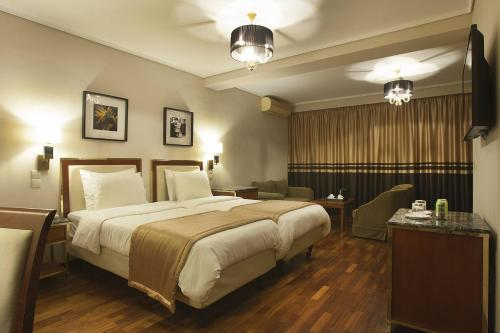 A bed or beds in a room at Ilisia Hotel