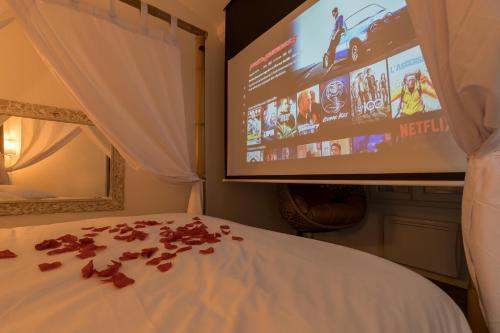 A television and/or entertainment centre at Urbinn Flat - La Suite d'Aphrodite, Jacuzzi, Sauna