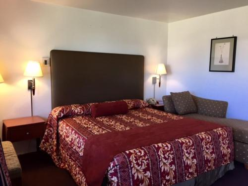 A bed or beds in a room at Maple Inn and Suites Los Banos