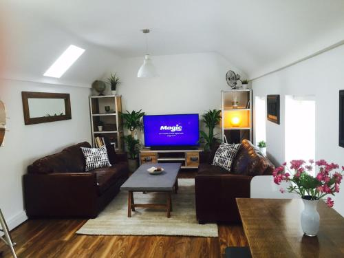 A television and/or entertainment center at Harpenden House Apartment 4