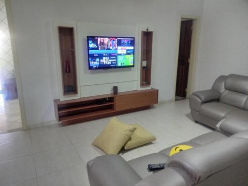 A television and/or entertainment center at Casa de Temporada com Piscina