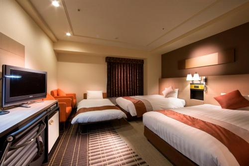 A bed or beds in a room at Meitetsu New Grand Hotel