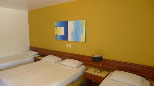 A bed or beds in a room at Sarana Praia Hotel