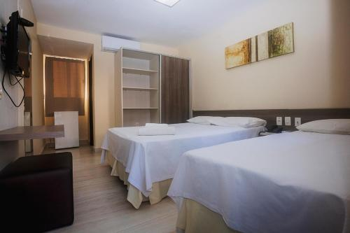 A bed or beds in a room at Alimar Hotel