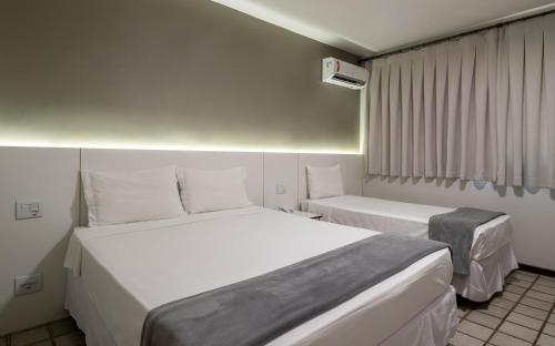 A bed or beds in a room at Carlton Suítes Limeira