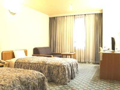 A bed or beds in a room at Hotel Gyokusen