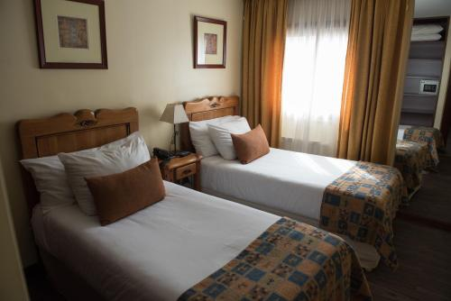 A bed or beds in a room at Del Bosque Apart Hotel