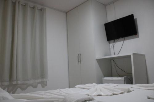 A television and/or entertainment centre at Pousada Kaluanã- Prospar Administradora