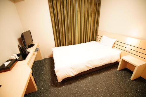 A bed or beds in a room at Dormy Inn Akita