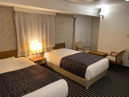 A bed or beds in a room at APA Hotel Osaka-Tanimachi