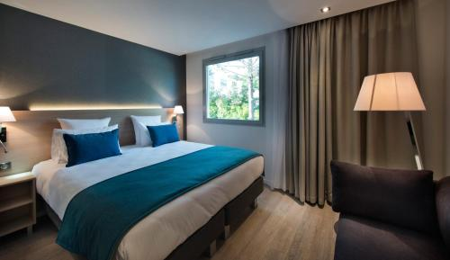 A bed or beds in a room at Golden Tulip Sophia Antipolis - Hotel & Spa