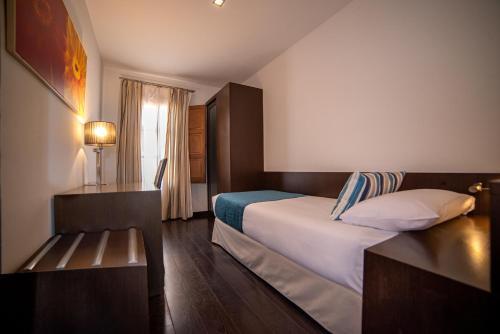 Cama o camas de una habitación en Apartamentos Pueblo Acantilado Suites