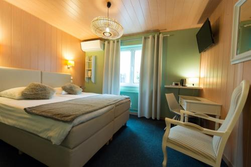 A bed or beds in a room at Hotel Restaurant Au Cheval Blanc