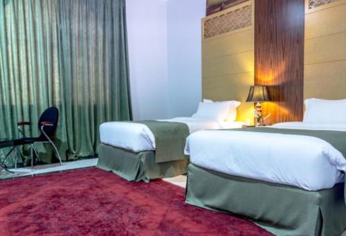 A bed or beds in a room at Doha Dynasty Hotel