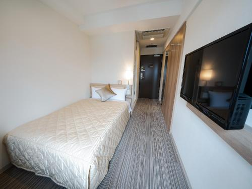 A bed or beds in a room at UNIZO INN Osaka Kitahama