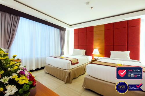 A bed or beds in a room at Royal Singosari Kuta