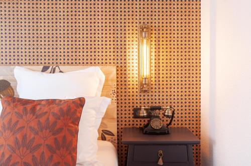 A bed or beds in a room at La Maison Hôtel Mulhouse Centre