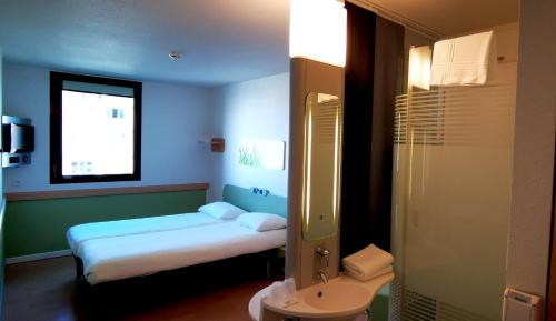 A bed or beds in a room at ibis budget Nimes Centre Gare