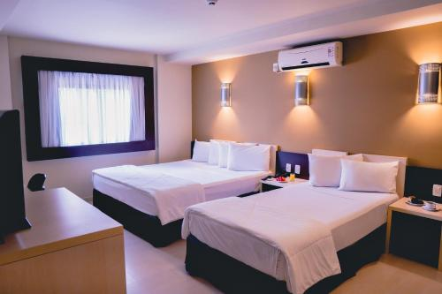 A bed or beds in a room at Master Curitiba Hotel - Centro - A 2km do Batel