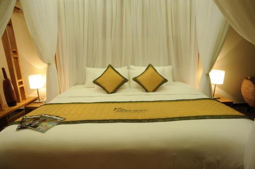 A bed or beds in a room at Aroma Beach Resort and Spa