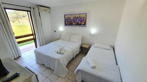 A bed or beds in a room at Hotel Termas Rio do Pouso